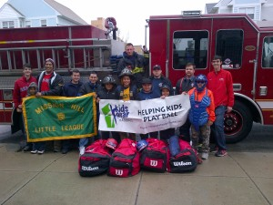 Mission Hill Little League players, along with Boston firefighters, pose with a large donation of equipment from Kids Gear for Baseball at this year's Opening Day celebration in April. (Courtesy Photo)